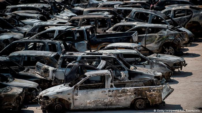 Burnt cars parked outside a football stadium following a wildfire in Rafina near Athens.