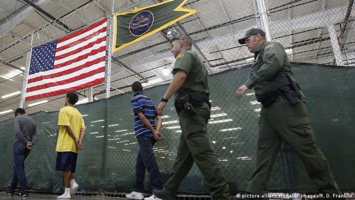 Young men walk with their hands behind their backs as US authorities follow (picture-alliance/dpa/AP Images/R. D. Franklin)