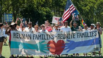 People hold a banner and flags demanded family reunification (picture-alliance/dpa/Pacific Press/G. Holtermann-Gorden)