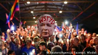 A protestor holds up a mask of PiS party leader Kaczynski with the word shame written on it