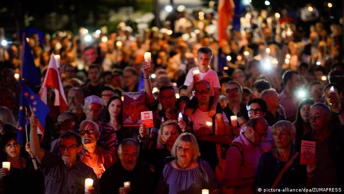 People demonstrate in Poland by holding flags, candles and cards