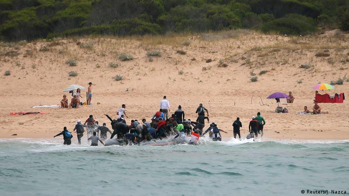 Беженцы высаживаются на испанском пляже после пересечения Гибралтара на надувной лодке