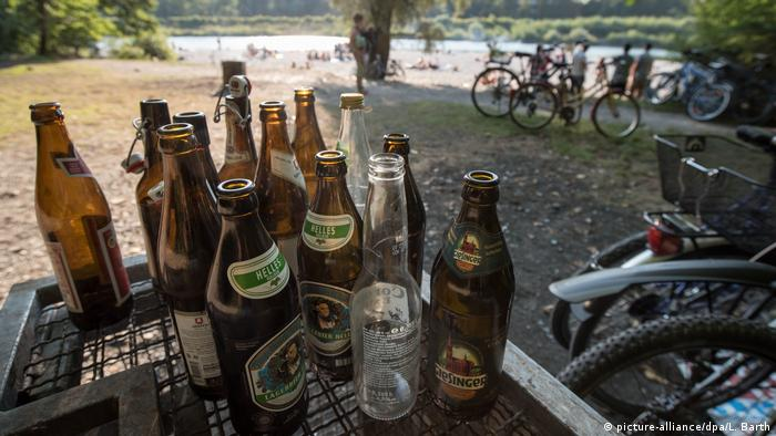 Collected beer bottles placed on a trash container in a park (picture-alliance/dpa/L. Barth)