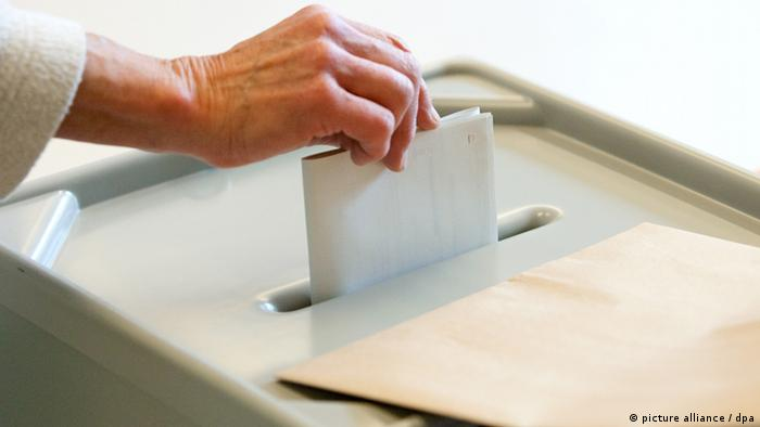 A person places a ballot paper into a ballot box (picture alliance / dpa)