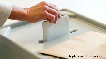 A person puts a ballot into a ballot box
