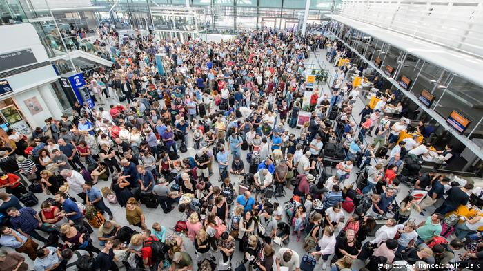 People pack the entrance area of Terminal 2 at Munich Airport after it was temporarily closed