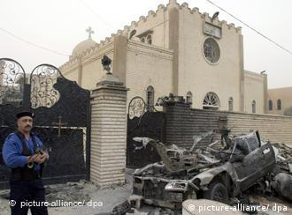 An Iraqi policeman stands guard at the site of a car bomb attack in front of a Christian church in Baghdad