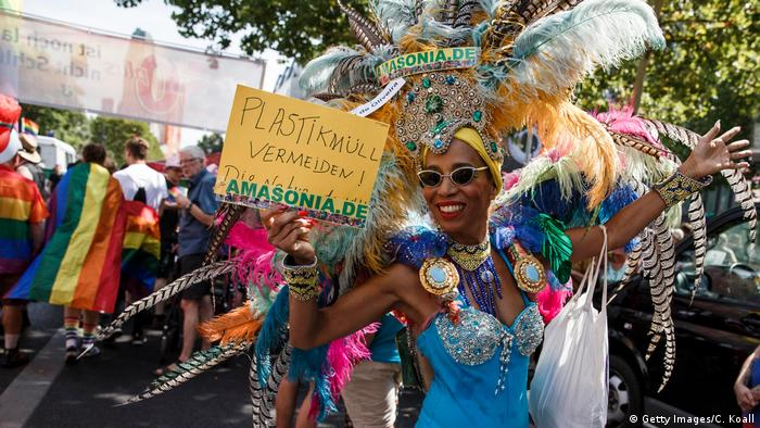 A costumed reveller holds a sign asking people to avoid plastic waste