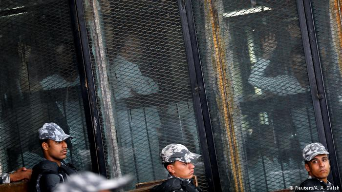 Defendants seen behind the mesh wiring of the metal cage inside the Cairo courtroom while security forces stand guard.