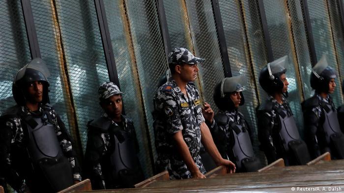 Polícia guarda réus atrás das grades durante o julgamento.