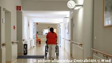***Archivbild*** Eine Krankenschwester schiebt einen Patienten im Rollstuhl auf einem Korridor in einer Klinik. Foto: Hans-Jürgen Wiedl/dpa-Zentralbild/ZB | Verwendung weltweit