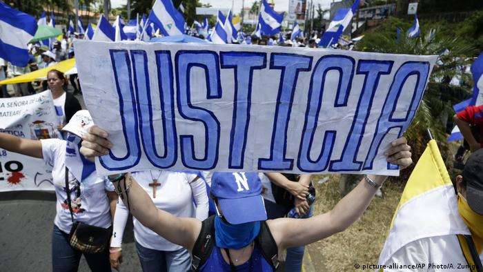 A demonstrator holds up a sign reading Justice in Spanish