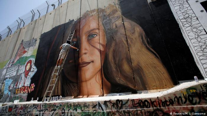 An artist paints on the Israeli wall a mural depicting Palestinian teen Ahed Tamimi (Reuters/M. I. Qawasma)
