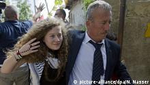 Palestinian Ahed Tamimi, left walks with with her father Bassem upon her arrival at their West Bank home village of Nebi Saleh, near Ramallah, Sunday, July 29, 2018. Ahed Tamimi and her mother Nariman were release today from an Israeli prison after serving an eight month sentence. (AP Photo/Nasser Nasser) |
