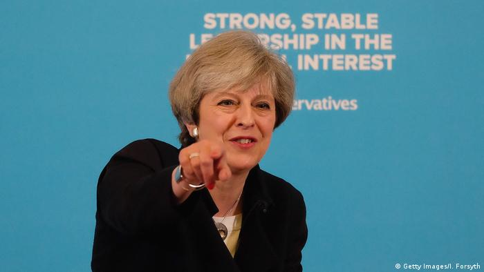Theresa May, in front of a slogan refering to strong, stable leadership in 2017, points at the audience of party supporters (Getty Images/I. Forsyth)