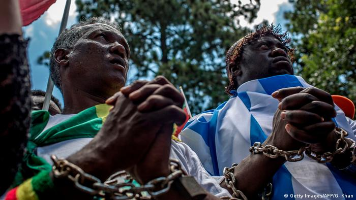 Two men in chains protest against the slave trade in Libya