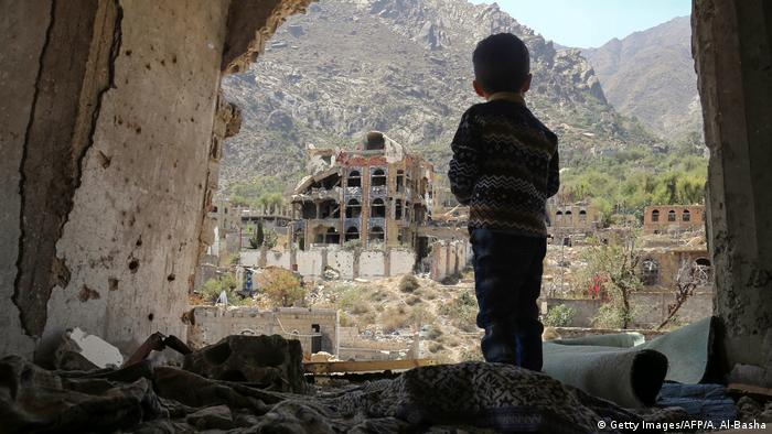 A Yemeni child looking out at buildings that were damaged in an air strike in the southern Yemeni city of Taez