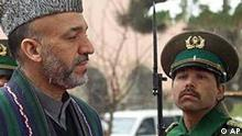 Interim Prime Minister Hamid Karzai walks past an honor guard during an official ceremony in the presidential palace in Kabul, Afghanistan, Friday Feb. 22, 2002 as the nation begins celebrating the Islamic holiday of Eid al-Adha, the Feast of the Sacrifice. (AP Photo/Mikhail Metzel)