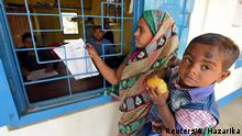 FILE PHOTO: A woman carrying her son arrives to check her name on the draft list of the National Register of Citizens (NRC) at an NRC center in Chandamari village in Goalpara district in the northeastern state of Assam, India, January 2, 2018. Picture taken January 2, 2018. REUTERS/Anuwar Hazarika/File Photo