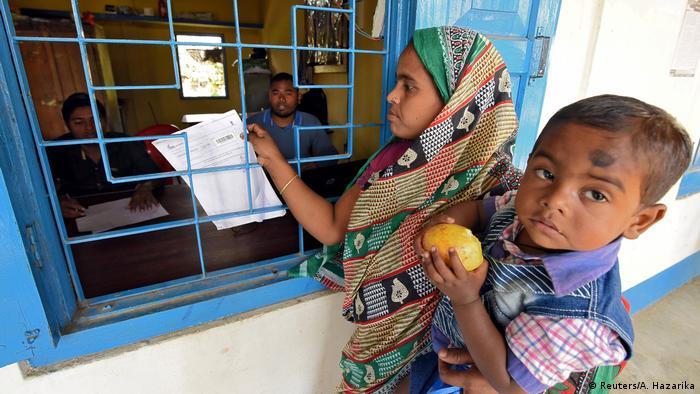 Assam eyaletinde nüfus sayımı taslak listesini inceleyen bir kadın ile çocuğu