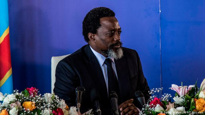 DRC President Joseph Kabila surrounded by flowers as he speaks into an array of microphones at a rare press conference in Kinshasa in January 2018