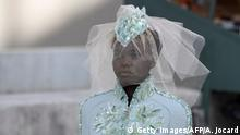 03.07.2018 South Sudanese-Australian model Adut Akech presents a creation by Chanel during the 2018-2019 Fall/Winter Haute Couture collection fashion show at the Grand Palais in Paris, on July 3, 2018. - For the 2018-2019 Fall/Winter Haute Couture collection, Chanel brings a replica of the French Institute (Institut de France) and French capital's green open-air book stalls (bouquinistes) along the banks of River Seine, to the Grand Palais in Paris. (Photo by Alain JOCARD / AFP) (Photo credit should read ALAIN JOCARD/AFP/Getty Images)