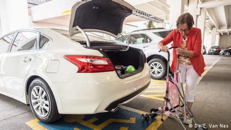 A woman packing a stroller into a car (DW/E. Van Nes)