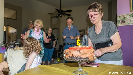 A group of people standing around a birthday cake (DW/E. Van Nes)