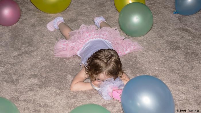 Seorang gadis berbaring di lantai dikelilingi oleh balon (DW/E. Van Nes)