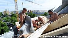 ARCHIV 2014 *** Bauarbeiter bringen am 20.05.2014 in Muenchen (Bayern) bei Dachdeckerarbeiten eine Folie als Dampfsperre auf dem Dach an. Foto: Tobias Hase | Verwendung weltweit