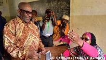 TOPSHOT - Comoros' President, Azali Assoumani arrives to a poll booth by an election official before casting his ballot during a constitutional referendum on July 30, 2018 at Mitsoudje polling station, outside Moroni capital of the Comoros archipelago off Africa's east coast. - Voters in the Comoros went to the polls on July 30 in a politically explosive referendum that could change the constitution and allow President Azali Assoumani to rule beyond 2021, his current term limit. (Photo by TONY KARUMBA / AFP) (Photo credit should read TONY KARUMBA/AFP/Getty Images)