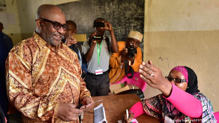 A smiling Azali Assoumani, in a printed shirt and sunglasses, talks to a woman seated at a desk,while photographers snap pictures of them
