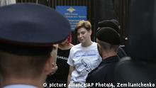 Olga Pakhtusova, a member of the feminist protest group Pussy Riot, is lead out of jail and into a police van in Moscow, Russia, Monday, July 30, 2018. Four members of the feminist protest group Pussy Riot, who had run onto the pitch dressed in police uniforms during the World Cup final were sentenced for two weeks. (AP Photo/Alexander Zemlianichenko)  