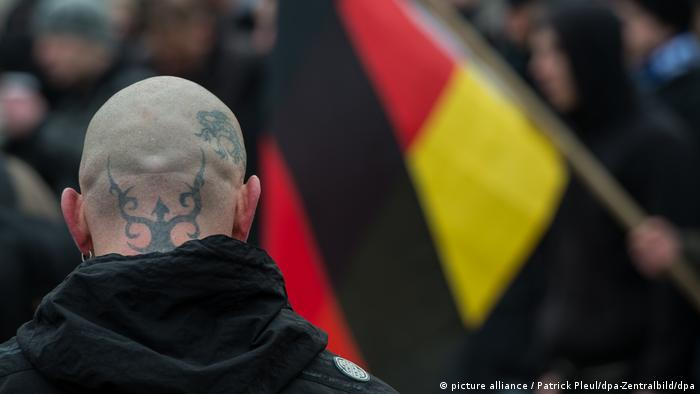 A German right-wing extremist at a rally, with a German flag in the background