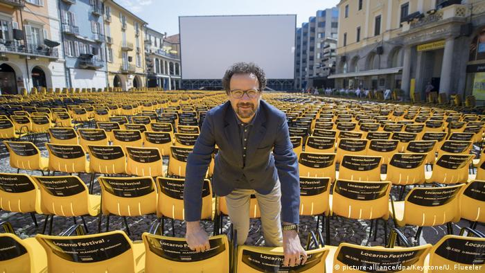 Carlo Chatrian surrounded by yellow chairs on Piazza Grande. (picture-alliance/dpa/Keystone/U. Flueeler)