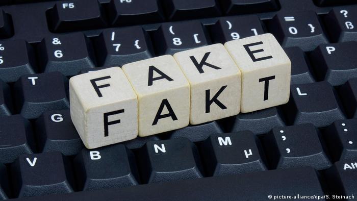 Сложенное из кубиков слово фейк лежит на клавиатуре компьютера