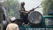 31.07.2018 An Afghan security personnel stands guard atop a vehicle near the site of suicide attack as an ongoing attack between Afghan security force and suicide attackers in Jalalabad on July 31, 2018. - Gunmen stormed a government building after multiple explosions in an ongoing attack in the eastern Afghan city of Jalalabad on July 31, an official said. At least two explosions were heard before the attackers entered the refugees and repatriation department compound, provincial governor spokesman Attaullah Khogyani said. Several international organisations are also in the vicinity. (Photo by NOORULLAH SHIRZADA / AFP) (Photo credit should read NOORULLAH SHIRZADA/AFP/Getty Images)