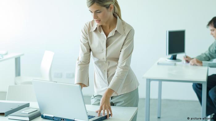 Офісна працівниця стоїть за робочим столом