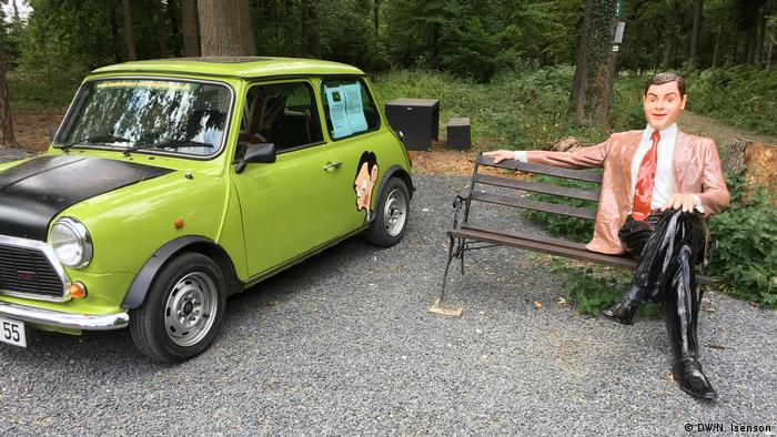A statue of Mr. Bean on a bench next to his black and green Mini