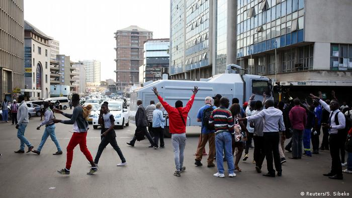Supporters of the MDC stand in front of a water cannon truck in the street (Reuters/S. Sibeko)