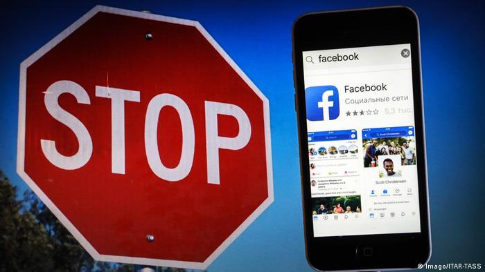 Знак Стоп на фоне смартфона с открытым Facebook