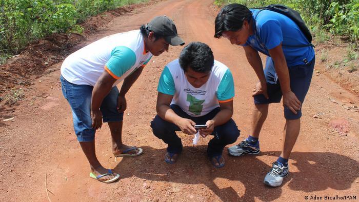 Drei Männer sehen auf ein Smartphone (Quelle: Ádon Bicalho/IPAM)