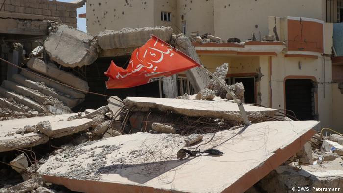 Sincar'daki bir enkazın üzerinde Şii milis gücü Haşdi Şabi'nin bayrağı dalgalanıyor.