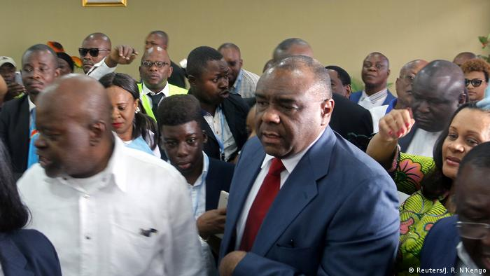 Jean-Pierre Bemba (right), in a blue suit and red tie, surrounded by men and women
