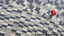 Bei Regen geht eine Passantin am Dienstag (26.06.2007) über den in verschiedenen Grautönen gepflasterten Platz vor dem Wiesbadener Hauptbahnhof. Das Wetter zeigt sich eher unangenehm mit Wolken und Regen bei Temperaturen um 15 Grad. Foto: Frank May dpa/lhe +++(c) dpa - Report+++ | Verwendung weltweit