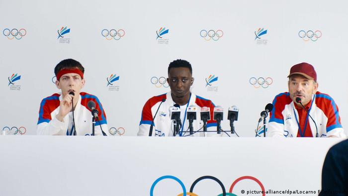 Filmstill Les Beaux Esprits: a man and two boys hold a press conference (picture-alliance/dpa/Locarno Filmfestival)