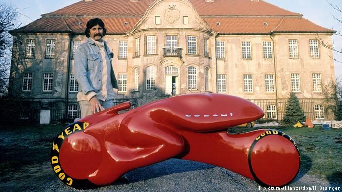 Designer Luigi Colani standing with a red racing model in front of a palace (picture-alliance/dpa/H. Ossinger)
