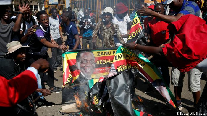 Supporters of the opposition Movement for Democratic Change party (MDC) of Nelson Chamisa burn an election banner