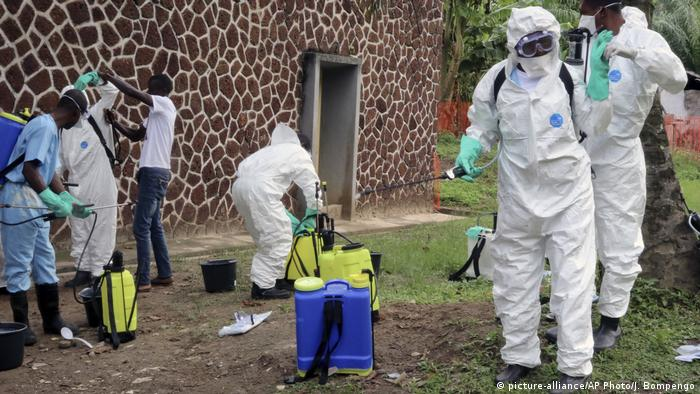 DRC health officials wearing protective clothing and equipped with disinfectant l