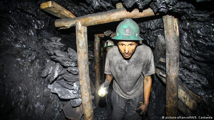 A man makes his way through a dark mine (picture-alliance/AA/S. Castaeda)